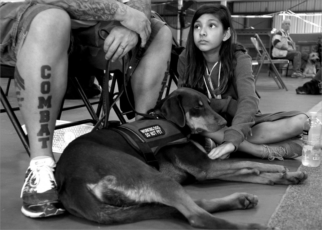 Carlos Vera, his daughter, and service dog Ruthie. Families are encouraged to join in the veteran/service dog training program so that they all can participate in the healing journey.