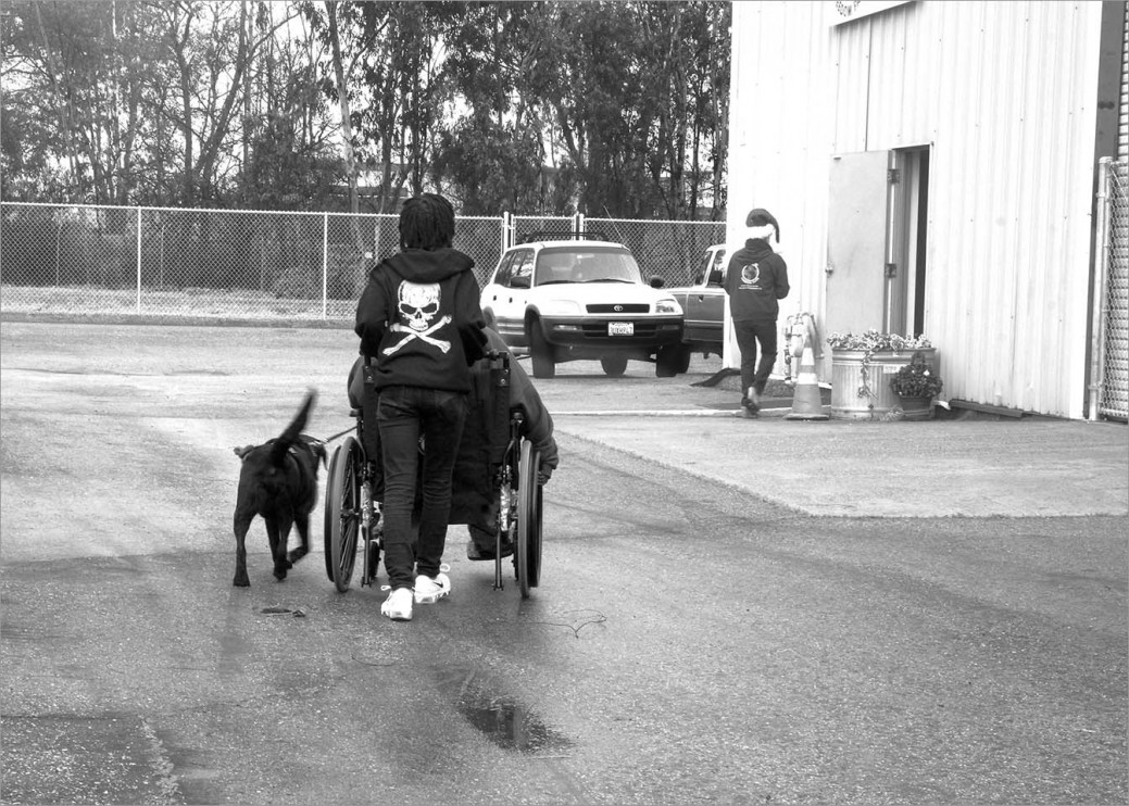 Veteran Leah Montoya, her daughter and service dog Rufus head into the main building at Operation Freedom Paws for the last training exercises of the day. Ahead of them is Phyllis a tireless supporter of OFP dressed as Santa's elf. She is there for every holiday with home baked goodies and special treats, for people and dogs alike.